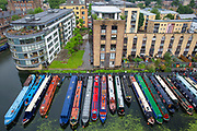 A line of narrow boats moored in the Battlebridge Basin on Regents Canal. Kings Cross, London, United Kingdom.