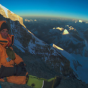 Jesse Rickert rests at sunrise at Mushroom Rock, 28,250 feet, on Everest's Northeast Ridge, Tibet.