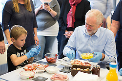 © Licensed to London News Pictures . 24/09/2016 . Liverpool , UK . JEREMY CORBYN makes pizza breads with ALFIE RAY (seven from Leasowe) (l) during a visit to Beaconsfield Community House in Birkenhead , following his victory declaration . The centre provides clothes and food that would otherwise be destined for waste from supermarkets , to local residents in need . Photo credit : Joel Goodman/LNP