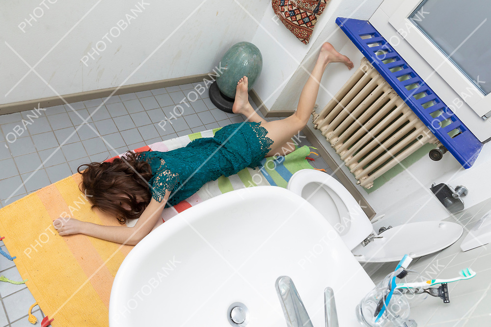 Young woman lying in the bathroom after a bad fall, typical domestic accident situation