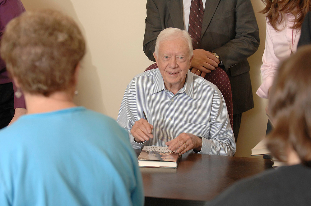 """Austin, TX December 14, 2006: Former U.S. President Jimmy Carter signs one copy of his latest book, """" Palestine Peace Not Apartheid"""" at a local bookstore where hundreds waited in line for a signed copy Friday morning. Carter signed over 1,200 copies of the book in two hours.       ©Bob Daemmrich/"""