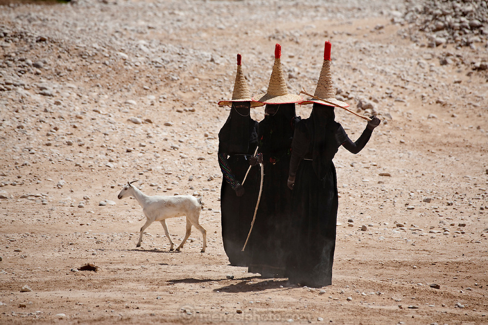 Three women dressed in black abayas and shielded from the hot desert sun in wide-brimmed straw hats called nakhls, and even gloves, tend goats near Shibam, on the edge of the Arabian Peninsula's Rub al Khali, or Empty Quarter. (From the book What I Eat: Around the World in 80 Diets) This section of the Arabian Desert holds the world's largest stretch of sand. Further north into Saudi Arabia, this desert contains some of the world's richest oil and gas fields. Though modestly dressed, the women aren't adverse to throwing stones to keep their goats close by?or to keep strangers with cameras away.