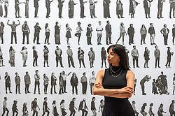 """© Licensed to London News Pictures. 02/06/2021. LONDON, UK. A staff member poses with """"The Chronicles of New York City"""", 2019, by JR. Preview of """"JR: Chronicles"""" at the Saatchi Gallery.  It is the largest solo museum exhibition to date of the internationally recognised French artist JR, featuring some of his most iconic projects from the past fifteen years.  The exhibition runs 04 June - 03 October 2021.  Photo credit: Stephen Chung/LNP"""