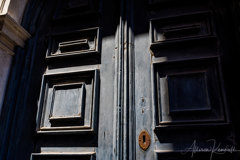 Detail of a faded blue door, illuminated by a patch of bright sun and texture emphasized by deep shadow