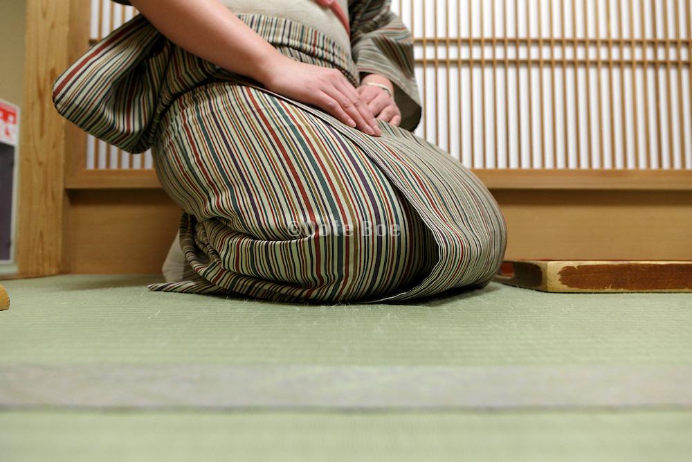 woman wearing kimono sitting on a tatami mat floor