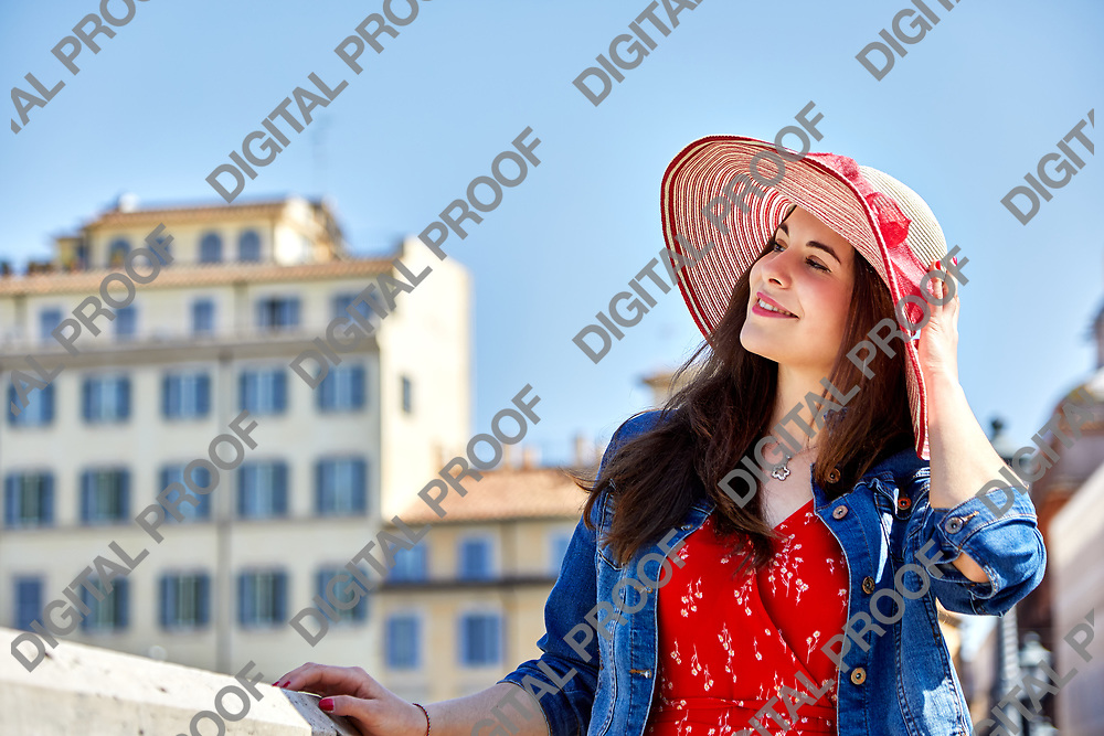 Cheerful woman touching hat and looking away on sunny old town street.