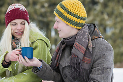 Young couple with coffee cup in snowy landscape in winter, Bavaria, Germany