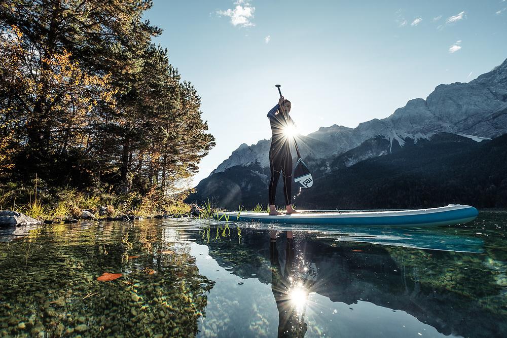 Junge Frau paddelt am SUP Board in der Morgensonne über den Eibsee, Blick zur Zugspitze, Garmisch-Partenkirchen, Bayern, Deutschland. * Young woman stand-up-paddling on Lake Eibsee in the morning light, overlooking the Zugspitze Mountain, Garmisch-Partenkirchen, Bavaria, Germany.
