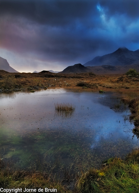 Rainstorms over the Cuillin Mountains with light coming in through the clouds on the Isle of Skye, Scotland.