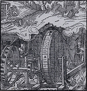 Ventilating a mine.  Hollow drum with air holes, B, at opposite sides, mounted on an axle, C, to which are fixed fans rotating inside the drum. Axle turned by water wheel through a spur gear and lantern. When axle turned, the fans rotating inside the drum would suck air in one hole and out of the opposite one, setting up a current of air.   From 'De re metallica', by Agricola, pseudonym of Georg Bauer (Basle, 1556).  Woodcut.