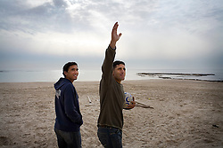 Former Israeli national soccer teammates Tomer Eliyahu, and Abbas Suan hang out on the beach in Jaffa, Israel, Feb. 1, 2006. Near by is Bloomfield Stadium, one of the many arenas they have played in together. The two friends don't let the fact that they are Jewish and Muslim respectively, get in the way of their love for the game. Suan, himself an Israeli-Arab, still faces racist criticism resulting from the unsettled conflict between the Israelis and Palestinians.