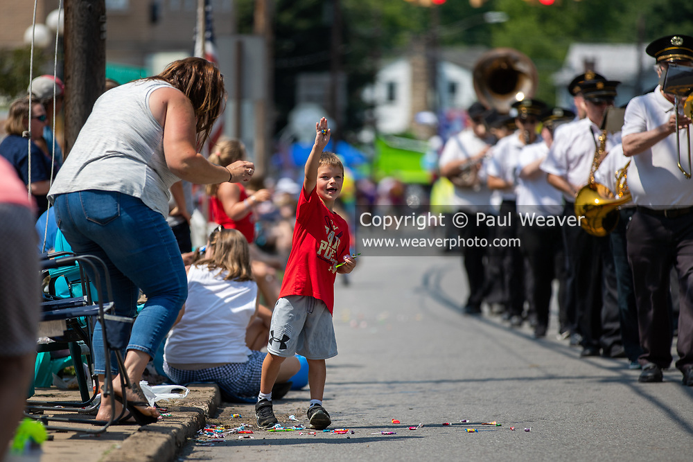 A child holds up a piece of candy thrown to him during the Independence Day parade in Millville, Pennsylvania on July 5, 2021.