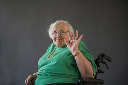 Portrait of senior woman sitting in wheelchair and waving hand, Bavaria, Germany