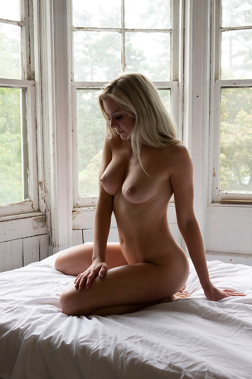 Shapely nude woman sitting on a bed illuminated by window light