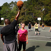 """A.J. Staley, of Hilton Head Island, trainer with Live In Fitness Camp, left, holds a basketball just out of reach of camp participant Nicki Mann, of U.K., center, while playing a game of basketball at Chaplin Community Park on Hilton Head Island on March 26, 2015.  """"I love basketball, I never played it growing up... but I have to rely on my speed because of my height,"""" said Mann."""