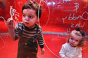 """2-year-old Paul Matrecano, left, gets a little too close, pressing his nose against the """"Inside Out Wall"""" as he scribbles away with Crayola Glass Markers, Saturday, March 16, 2002.  The special glass enclosed structure at the Crayola Factory at Two Rivers Landing, in Easton, Pennsylvania, is designed to allow patrons to create their own graffitti with markers that are easily erased.  Sitting on right, observing, is 2-year-old Sara Moorhead of Oyster Bay, New York."""