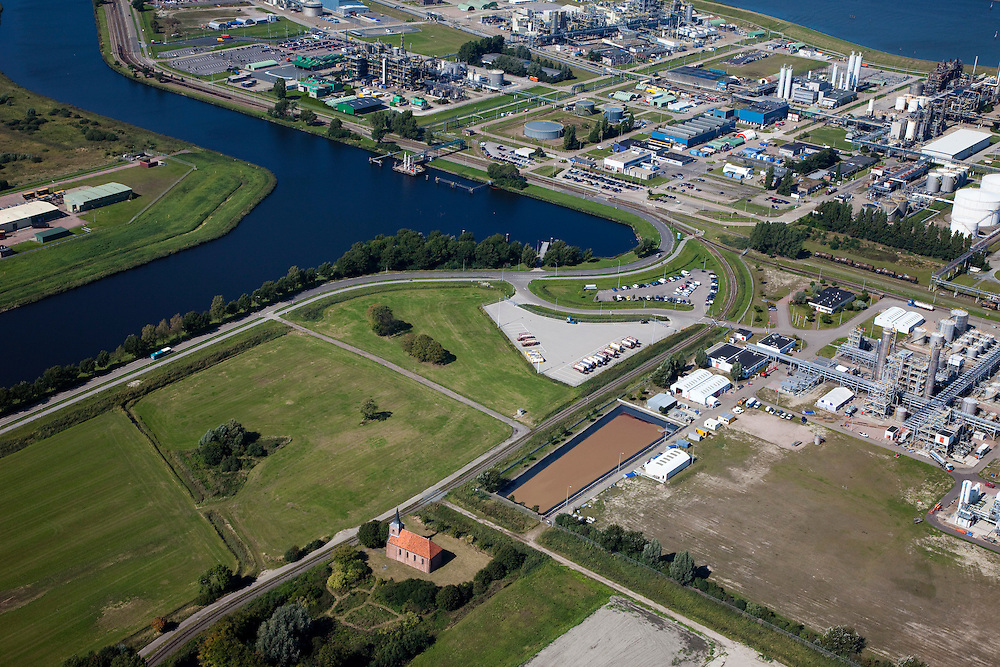 Nederland, Groningen, Delfzijl, 08-09-2009; Industrieterrein Eemsmondgebied met Chemie park. Het kerkje met dak van rode pannen is dat van het verdwenen dorpje Heveskes dat in het verleden ruimte moet maken voor het industrieterrein. Chemiepark.nl  huisvest onder andere AkzoNobel (soda, chloor, zout)..Industrial Estate of the Eemsmond area with aluminum smelter Aldel (aluminum Delfzijl) right, to the left part of the Chemical Park. The little church with red roof tiles belongs to the village Heveskes, the village had to make room for the for the industrial park in the past Chemiepark.nl houses  Akzo Nobel (soda, chlorine, salt).luchtfoto (toeslag); aerial photo (additional fee required); .foto/photo Siebe Swart