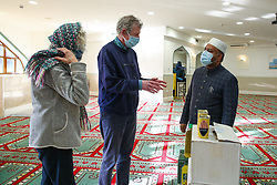 © Licensed to London News Pictures. 01/12/2020. London, UK. IMAM ABDUL KADIR (L) and members of the Gospel Church at the London Islamic Cultural Society, also known as Wightman Road Mosque in north London as they donate halal food to the FoodBank at the Gospel Church. Muslim families visiting the foodbank during the COVID-19 lockdowns have appealed for help with food items, especially halal food. Photo credit: Dinendra Haria/LNP