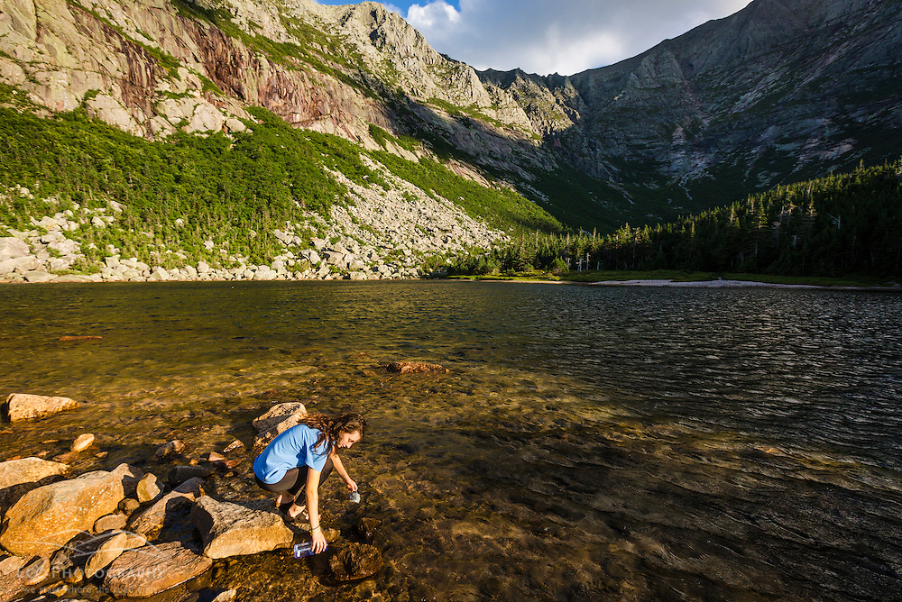 A teenage girl fills a bottle of water in Chimney Pond in Maine's Baxter State Park.