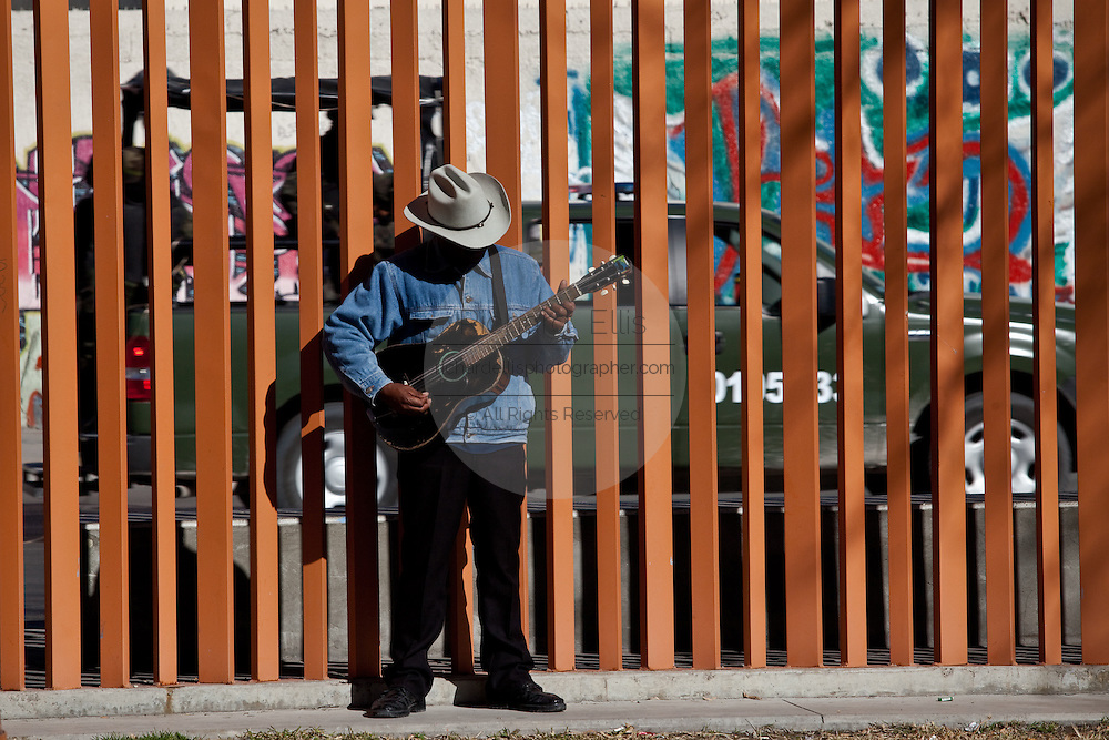 A guitar player practices in Benito Juarez Park as a Mexican Army patrol drives behind January 17, 2009. The heavily armed military patrols the city to help stem the violence in the ongoing drug war which has already claimed more than 40 people since the start of the year. More than 1600 people were killed in Juarez in 2008, making Juarez the most violent city in Mexico.    (Photo by Richard Ellis)