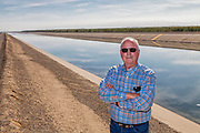 Rod Cardella stand in fron of the California Aqueduct next to his farm. Rod Cardella runs Cardella Winery, a family business since 1969, which grows almonds, broccoli and other crops as well as grapes. With the high price of water in recent years, Rod has turned to technology and drip irrigation to lower water usage and like many other farmers is planting high value crops such as almonds. Fresno County, San Joaquin Valley, California, USA