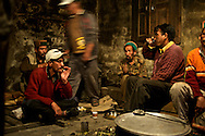 A group of men gather to celebrate the arrangement of one man's daughter for marriage. They are drinking a local whiskey made from barley.