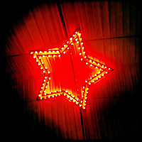 A hundred yellow light bulps form a 5 spike star against a red background