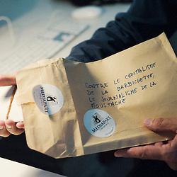 """PARIS, FRANCE. 14 SEPTEMBRE 2010. Edwy Plenel, nous presentent les objets qui font son quotidien de responsable de Mediapart, journal en ligne dont il est le co-fondateur. Ici, cadeau espiegle de ses collaborateurs durant """"l'affaire Bettencourt"""" et notamment les enveloppes de cash. (photo : Antoine Doyen)"""