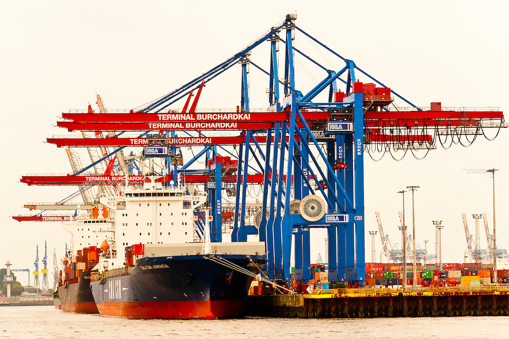 Shipping containers being unloaded from cargo ships in the harbor at Hamburg, Germany (second busiest harbor in Europe)