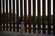 A young girl, part of a group of Central American migrants seeking asylum, walks along a stretch of border fence after crossing the Rio Grande near Penitas, Texas, U.S., April 6, 2019.