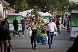 © Licensed to London News Pictures. 26/09/2021. London, UK. Members of the public carry exhibitors' plants on the last day of the 2021 Chelsea Flower show. A wide array of unusual and striking display items can be purchased on the closing day of The Royal Horticultural Society flagship flower show, held at the Royal Hospital in Chelsea since 1913. Photo credit: Ben Cawthra/LNP