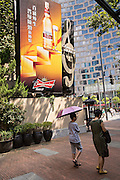 A mother and son walk past a beer ad in Xintiandi Plaza shopping district Shanghai, China
