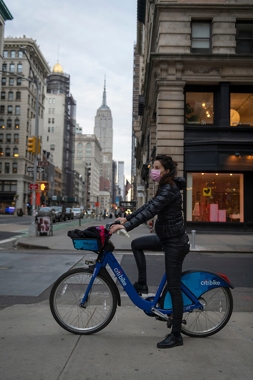 New York City, USA - March 20, 2020: Valentina Gaia, out for a bike ride, wears a precautionary face mask at 5th Ave & E 20th St in the Flatiron District of Manhattan.