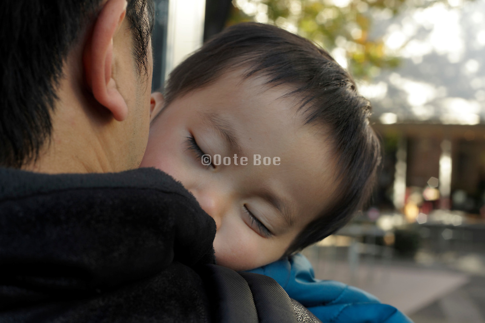 father walking with sleeping toddler Japan