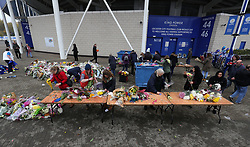 Volunteers help to relocate floral tributes, left for the victims of the Helicopter crash, to a new memorial site at the King Power Stadium, Leicester.