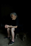 86 year old Cai Ximei sits in her home in a rural village near Fuyang, Anhui Province,  China on 28 August  2013.  As able-bodied adults seek work in cities in hopes of better income, more and more villages in China are inhabited mostly by the elderly and children.