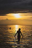 Meike, a 19-year-old German traveler, stands in the sea at sunset at Zen Beach, Ko Phangan, Thailand (June 2017)
