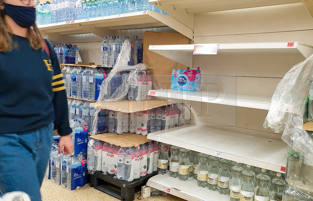 © Licensed to London News Pictures. 20/09/2020. London, UK. A shopper wearing a face covering walks past nearly empty shelves of bottled water in a Sainsbury's supermarket in London, as essential items start to run out, amid a possible second lockdown due to a rise in COVID-19  cases. Photo credit: Dinendra Haria/LNP