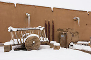 Martinez Hacienda with ancient cart and chili ristras in winter snow