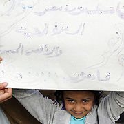 Small girl holds up a big sign, declaring that Gaza and Aqsa are next for the 25th January Youth.
