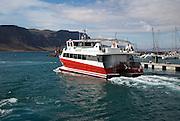 Tourist ferry boat Biosfera Express leaving the harbour Caleta de Sebo, La Isla Graciosa, with distant view of cliffs of Lanzarote, Canary Islands, Spain