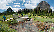 Backpackers cross a bridge over a tributory of Pharaoh Creek at Egypt Lake Campsite, in Banff National Park, Alberta, Canada. This is part of the big Canadian Rocky Mountain Parks World Heritage Site declared by UNESCO in 1984. Panorama stitched from 4 images.