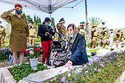 92 years old Ruchama Eliezer sits next to the grave of her fallen daughter, Carmela as IDF soldiers salute at Kiriyat Schaul Military Cemetery, Ramat Ha Sharon, Israel April 13, 2021.  Israel will commemorate this year's Memorial  in remembrance of it's soldiers who fell in the line of duty and of  and civilians who where killed in acts of terror. Services and ceremonies were cancelled during 2020 due to the coronavirus pandemic, this year, as vast percentage of the population are vaccinated, ceremonies will be able to take place in a some what ordinary manner.