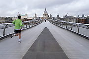 Man running over a very quiet Millennium Bridge towards St Pauls Cathedral as the national coronavirus lockdown three continues on 28th January 2021 in London, United Kingdom. Following the surge in cases over the Winter including a new UK variant of Covid-19, this nationwide lockdown advises all citizens to follow the message to stay at home, protect the NHS and save lives.