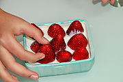 a hand is tempted by a bowl of Fresh strawberries and cream healthy snack