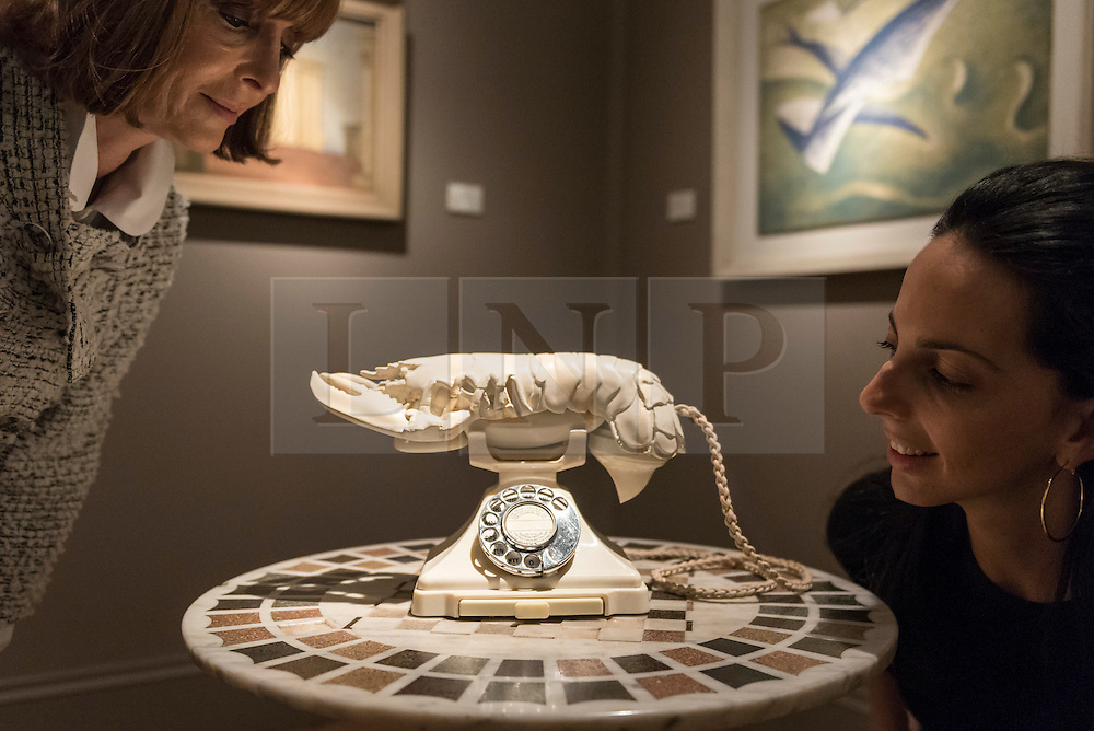 """© Licensed to London News Pictures. 29/06/2016. London, UK.  Visitors view """"Lobster Telephone (white aphrodisiac)"""" by Salvador Dali at the preview, in Chelsea, of Masterpiece London, the leading international fair for art and design from antiquity to the present day with works from 154 world-renowned exhibitors on sale.  The fair is open until 6 July.Photo credit : Stephen Chung/LNP"""