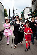 LONDON, ENGLAND, UK, JUNE 11TH 2011. Mother Louise Irwin-Ryan with her daughter Georgia (11, wearing a pink Lolita dress) and son Kiefer (8, wearing a red Liverpool Football Club kit) spending a day out together in Camden Town, North London. Louise is on various benefits to help support her family income, and housing, although recent government changed to benefits may affect her family drastically, possibly meaning they may have to move out of London. Louise Ryan was born on the Wirral peninsula in 1970.  She moved to London with her family in 1980.  Having lived in both Manchester and Ireland, she now lives permanently in North London with her husband and two children. Through the years Louise has battled to recover from a serious motorcycle accident in 1992 and has recently been diagnosed with Bipolar Affective Disorder. (Photo by Mike Kemp/For The Washington Post)