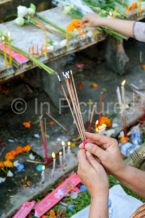 """Offering incense sticks at the That Luang festival, Vientiane, Lao PDR. Vientiane's most important Theravada Buddhist festival, """"Boun That Luang"""", is held for three days during the full moon of the twelfth lunar month (November). Monks and laypeople from all over Laos congregate to celebrate the occasion with three days of religious ceremony followed by a week of festivities, day and night. The religious part concludes as laypeople, carrying incense and candles as offerings, circumambulate Pha That Luang three times in honor of Buddha."""