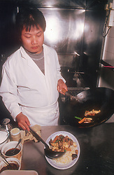 Chef dishing up stir fried meal from wok in kitchen of Chinese restaurant,