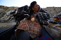 November 20, 2018 - Mexicali, Mexico - A young couple from Honduras with their 1-year-old baby hitch a ride with others from migrant caravan that had stopped to rest in Mexicali, Mexico. They endure the cold wind as they drove through La Rumorosa mountain road to a shelter in Tijuana where they will wait in hopes of crossing the border to America.  They started October 12 on their journey with caravan. (Credit Image: © Carol Guzy/ZUMA Wire)